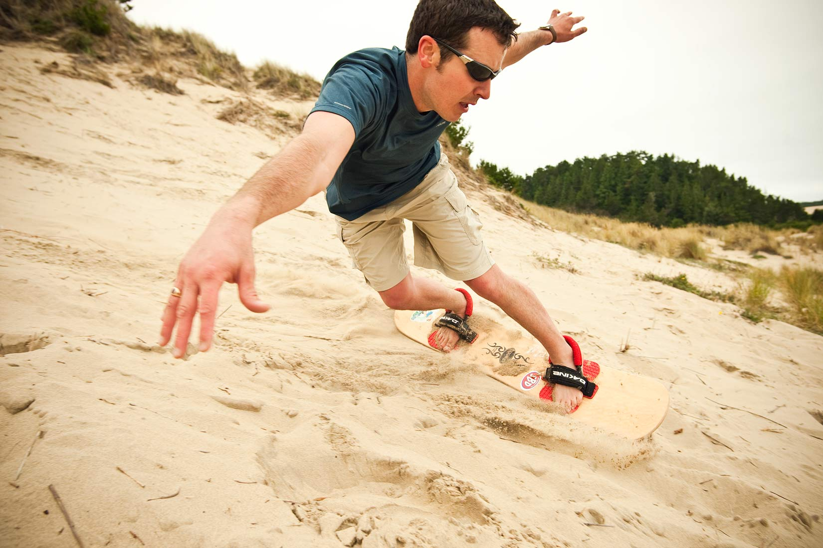 Advertising photographer Portland - man sand boarding on the Oregon coast