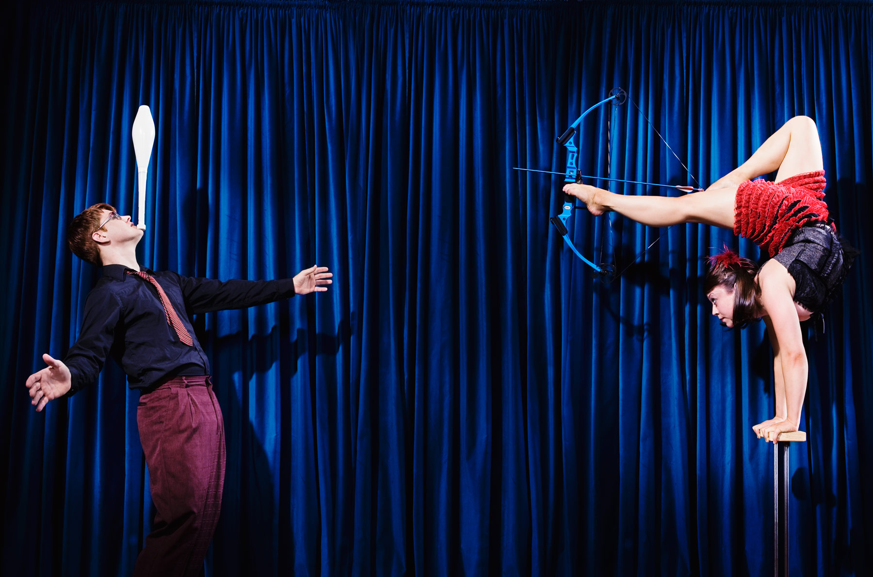 Portrait of circus performers doing a trick with the man balancing a pinball on his chin and the woman holding a bow and arrow with her feet while balancing on her hands