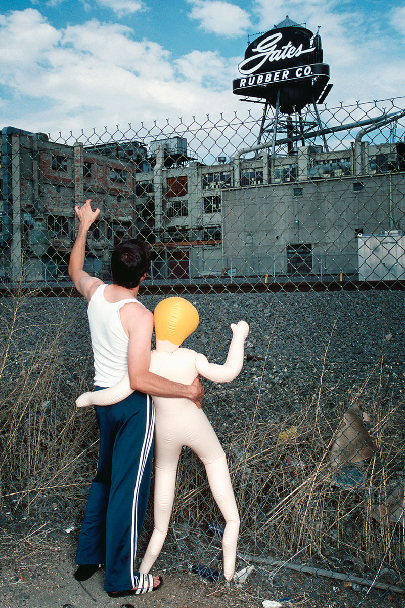 Conceptual portrait of a man and blow up doll embracing will view Gates Rubber Factory