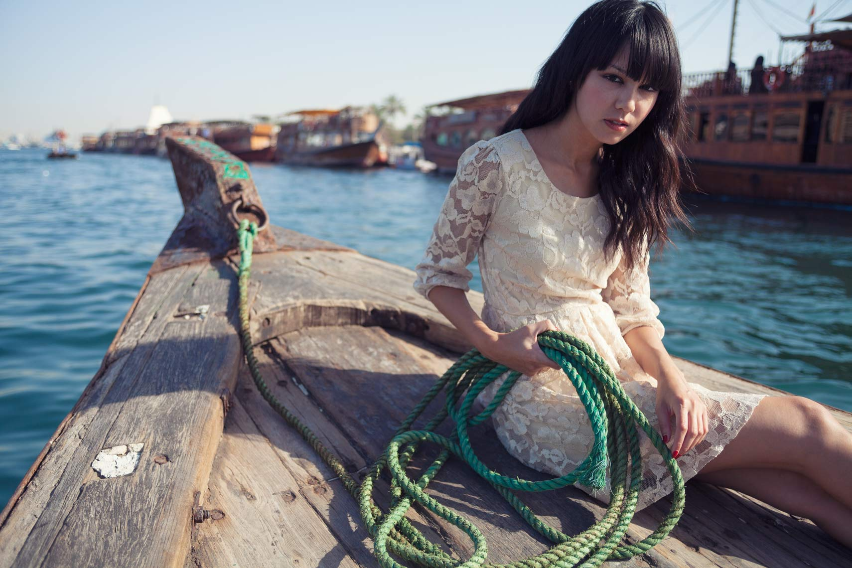 Fashion portrait of woman sitting on a boat holding a green rope in Dubai
