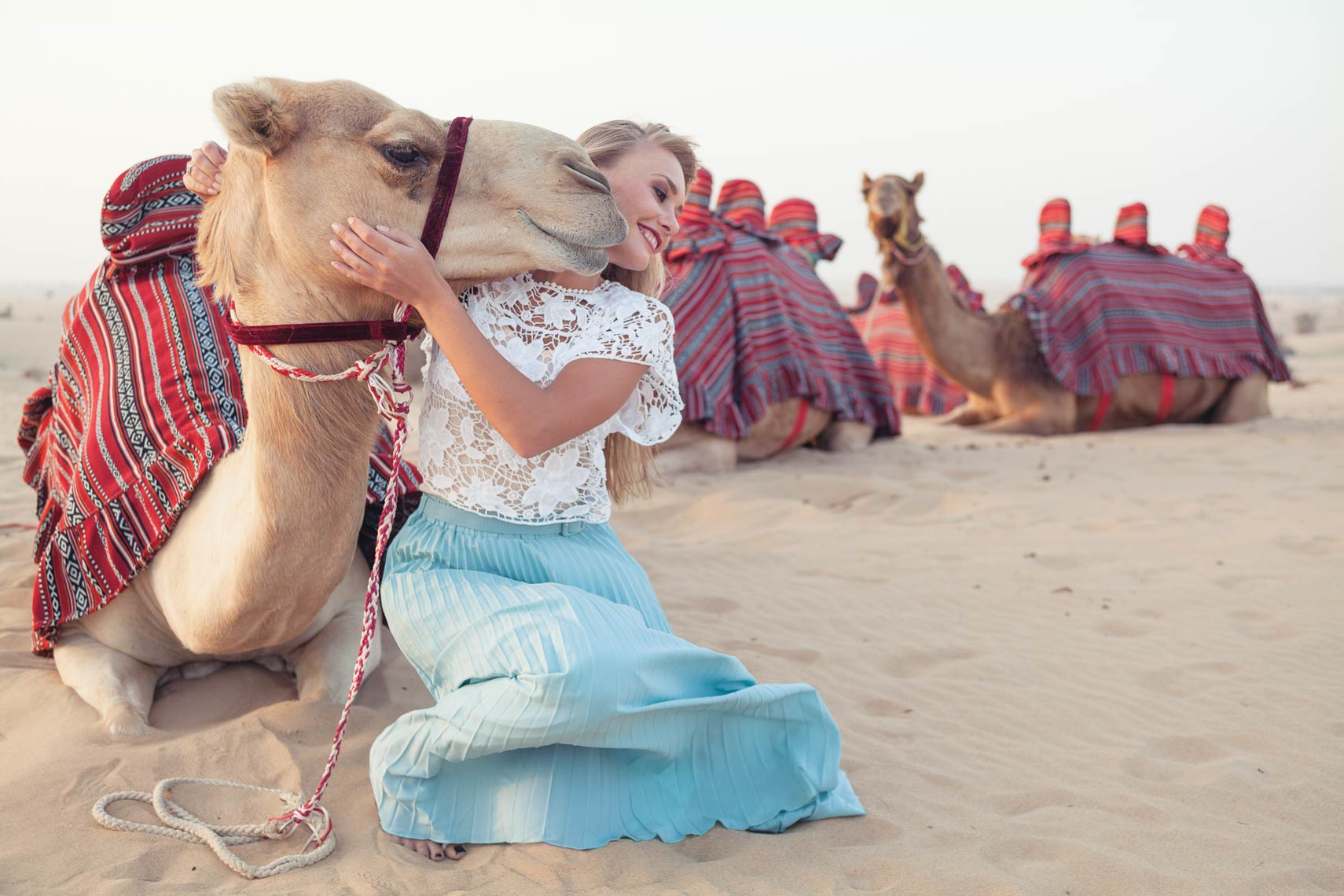 A woman with a camel kissing her face in the U.A.E. desert.