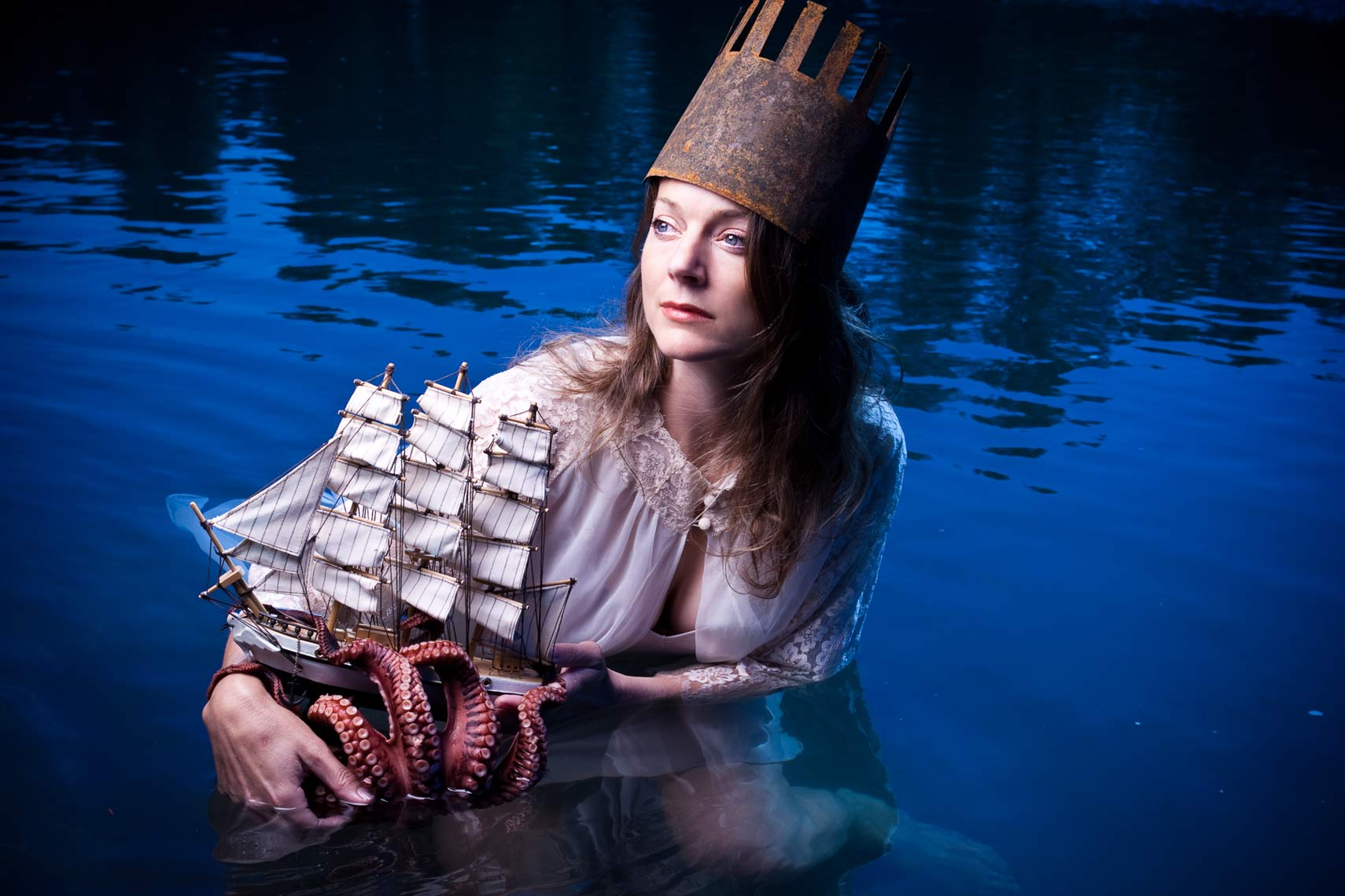 Portrait of a woman with a crown, her boat, and an octopus in water.