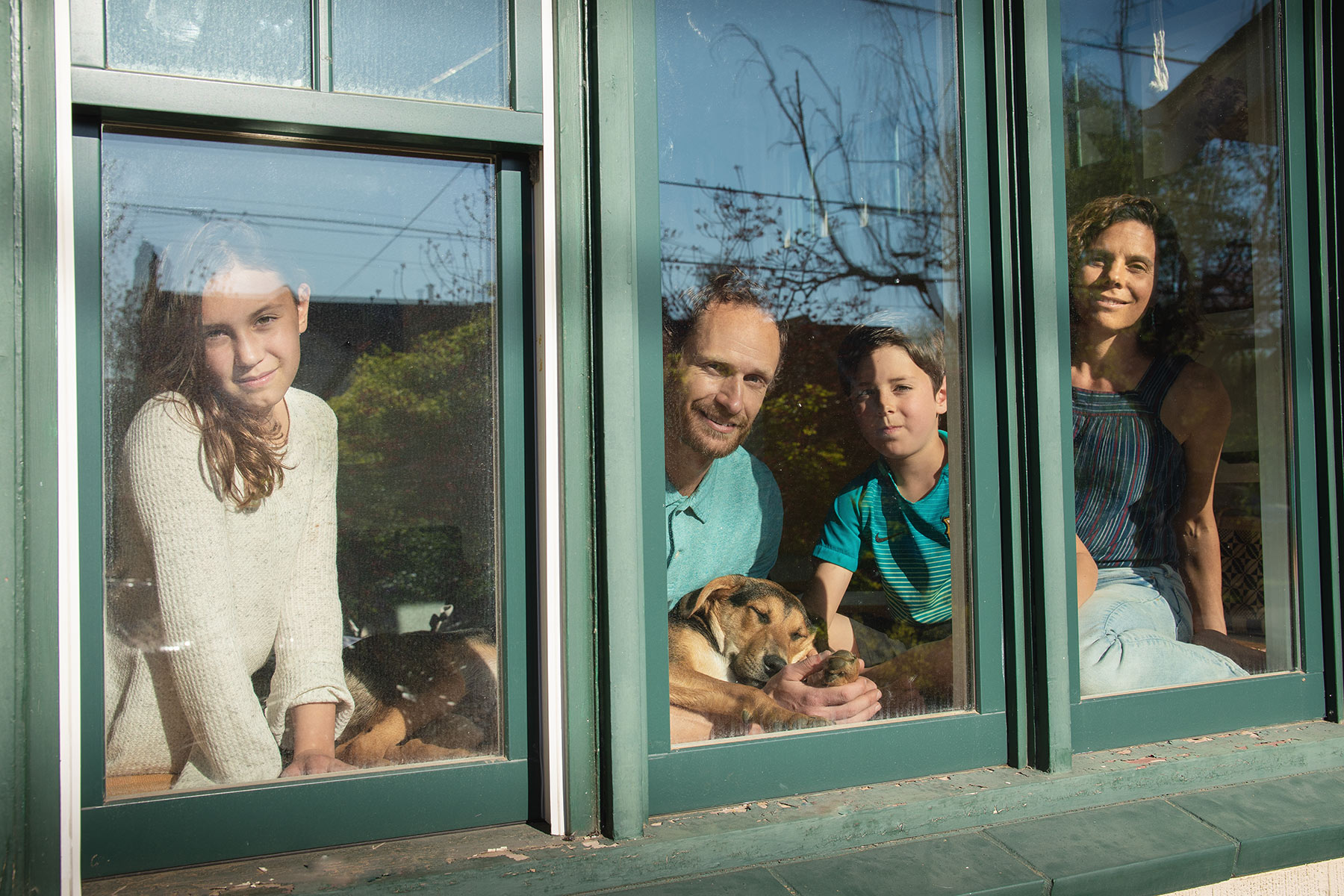 Documentary portrait of family at their front window