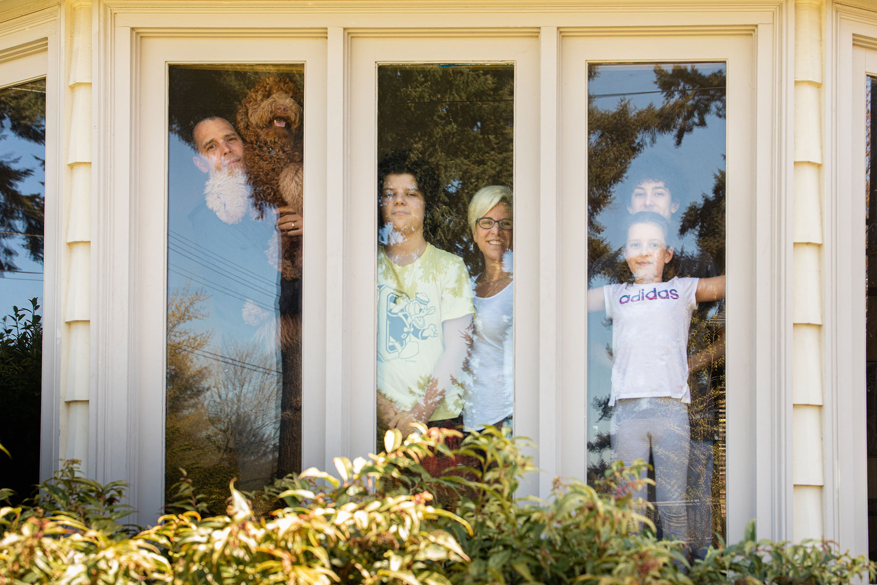 Portrait of family at their front windows during pandemic