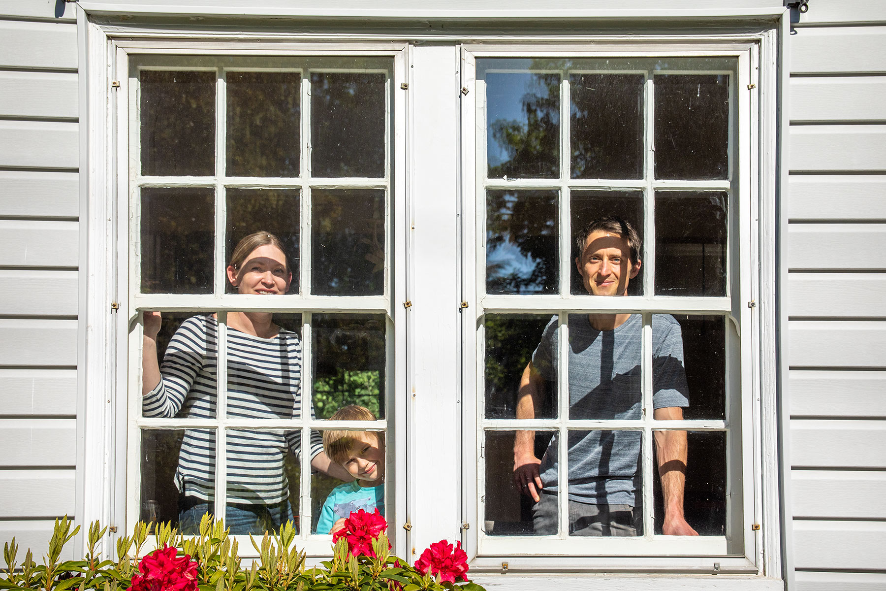 Editorial portrait of family in their window during COVID-19 outbreak