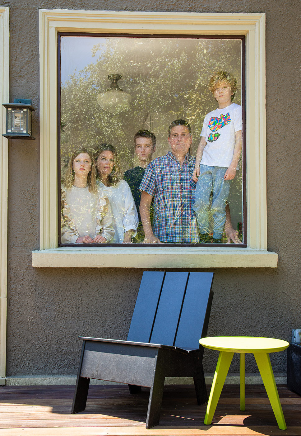 Editorial portrait of family at their window practicing social distancing