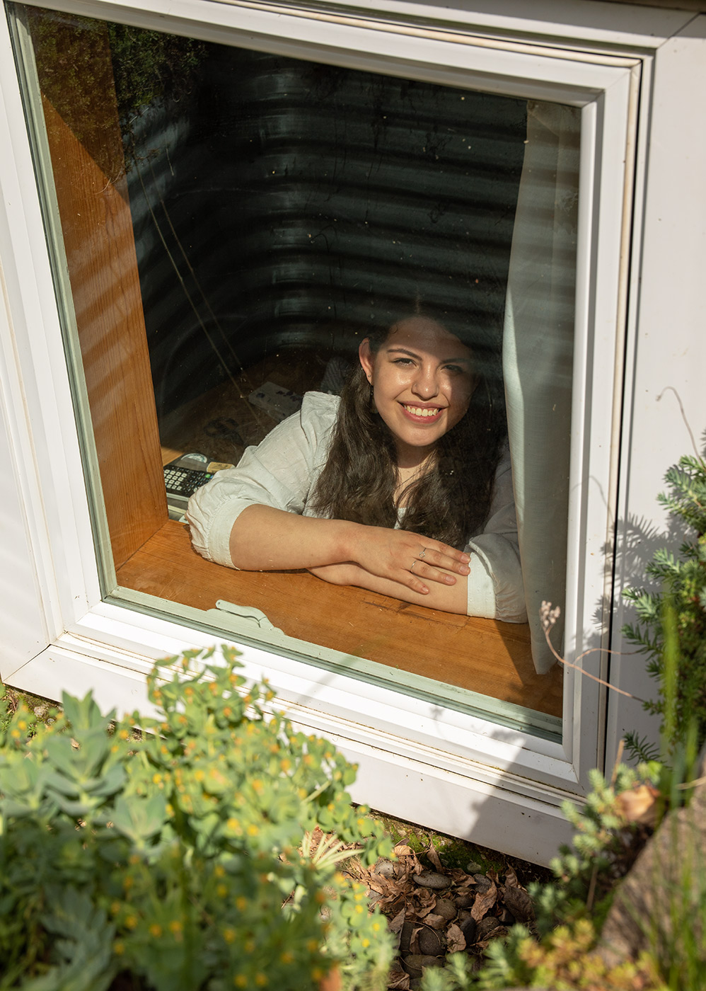 Documentary portrait of woman in her basement window