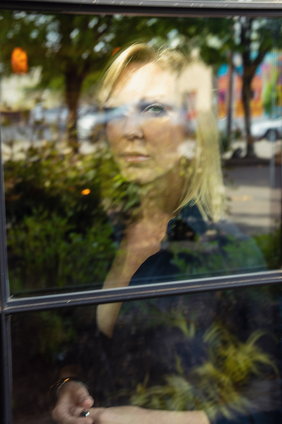 Editorial portrait of actress with window reflection of city street