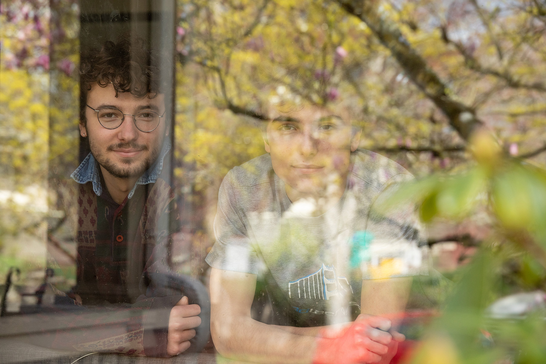 Portrait of brothers  at a window with outside reflection