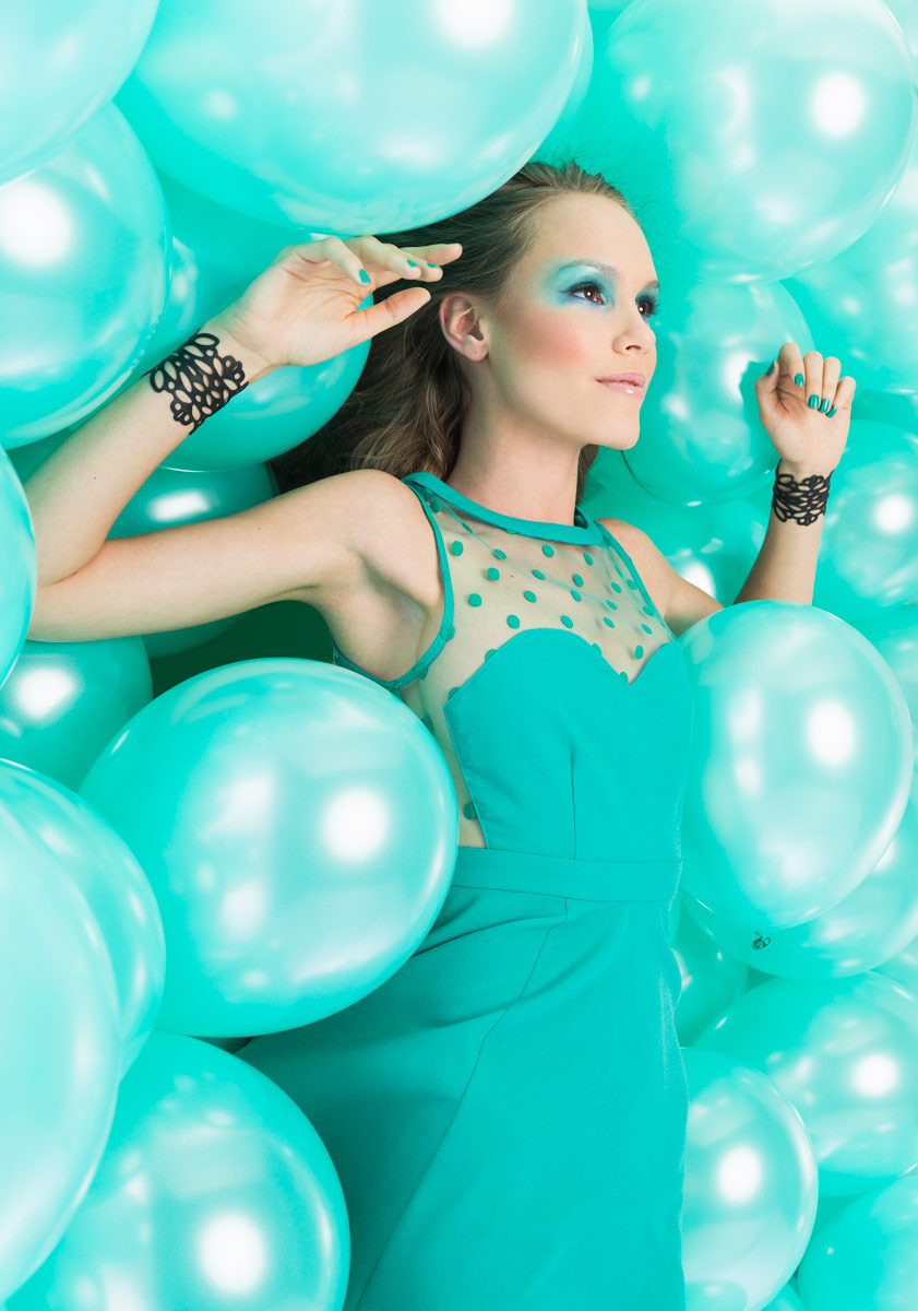 Woman surrounded by aqua colored balloons