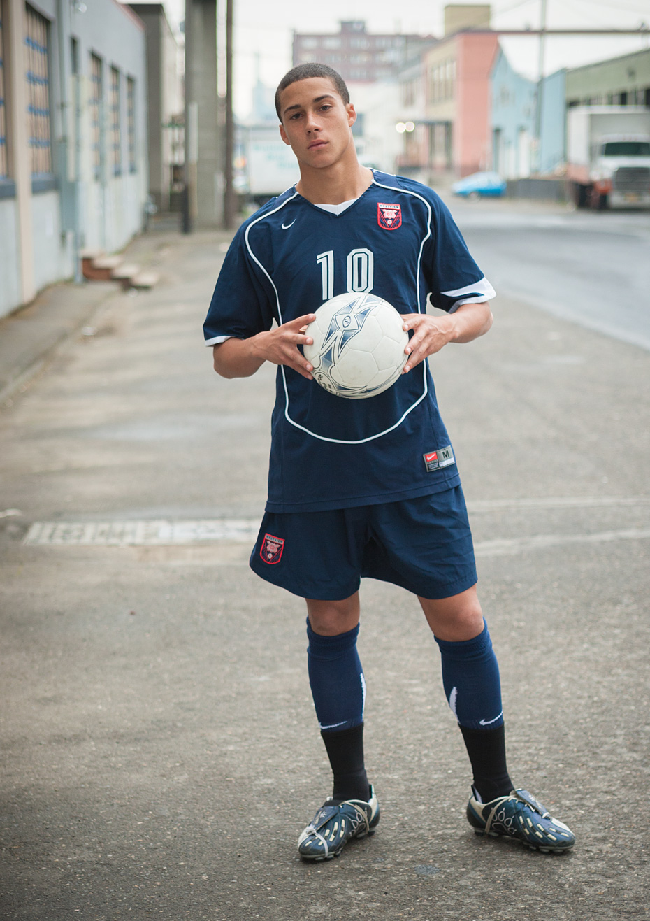 Commercial photographer Portland - soccer player holding ball in urban street