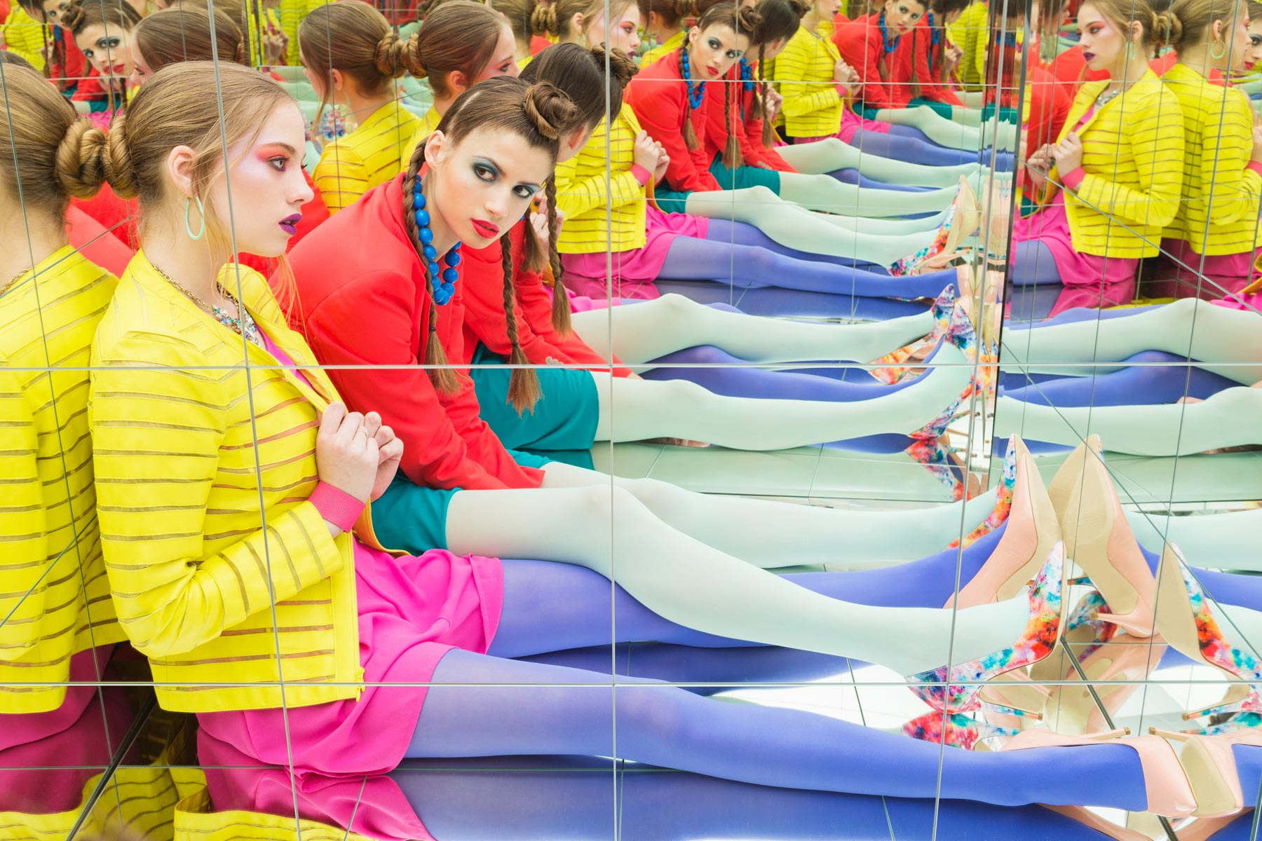 Conceptual fashion image of two woman with bright clothes in a mirror box by Michael Schmitt