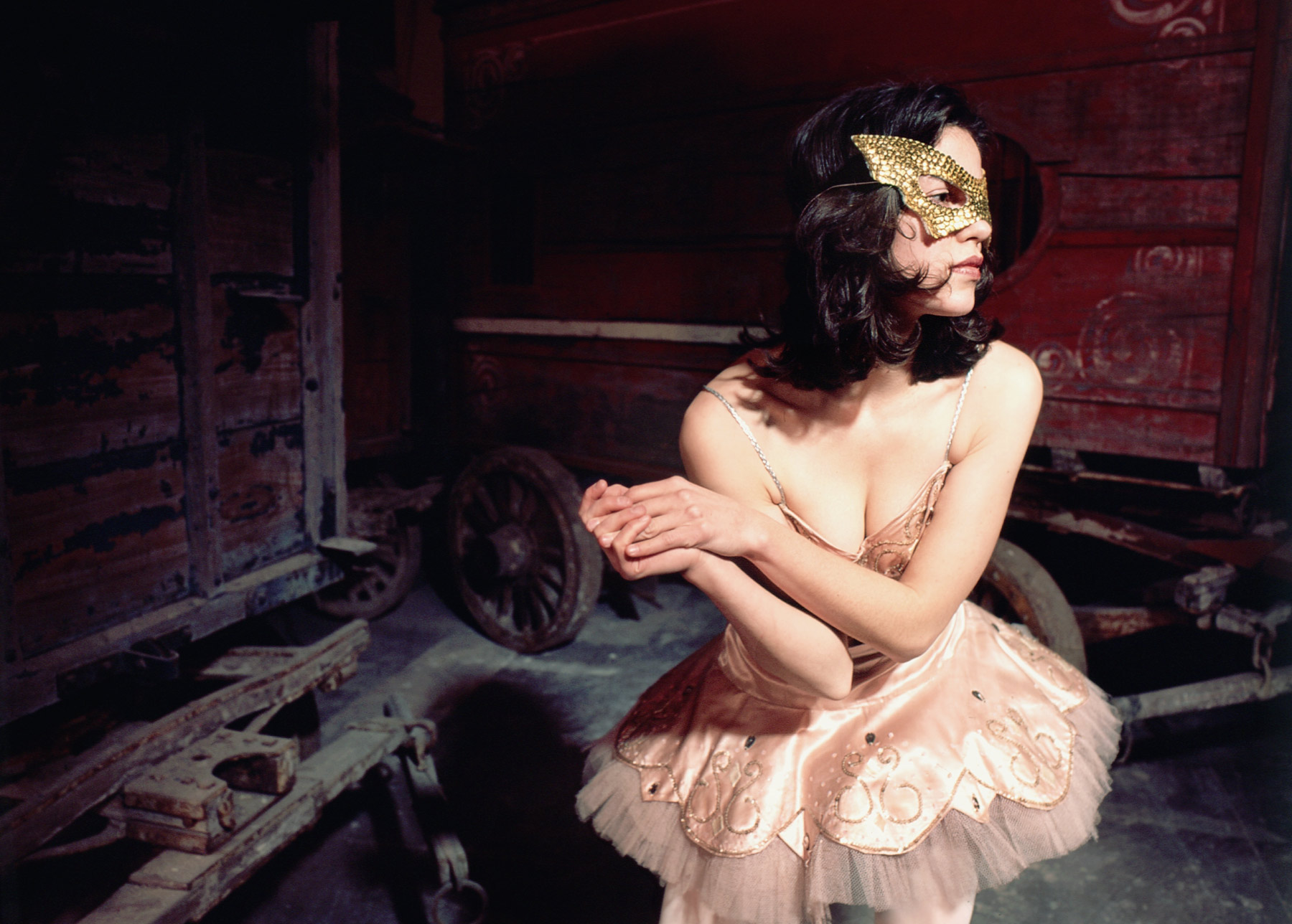 Conceptual portrait photography - woman wearing a ballerina costume and gold mask surrounded by vintage circus wagons.
