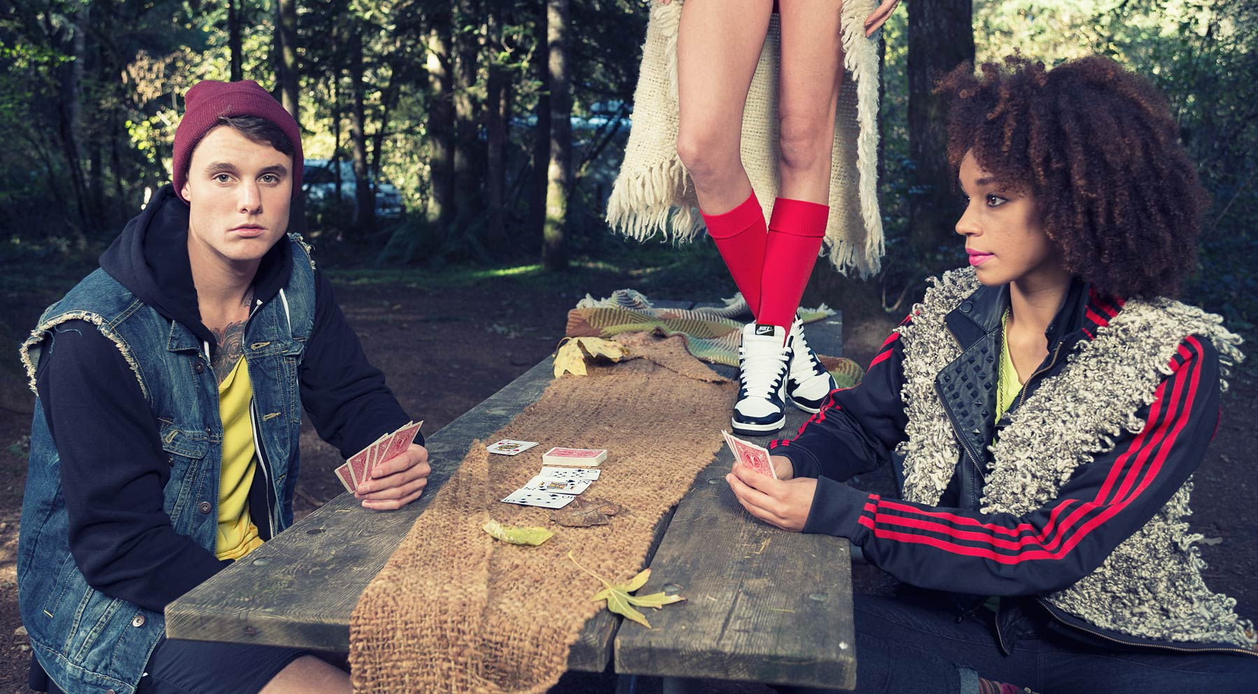 Fashion portrait of a couple playing cards at a camp ground with a woman standing behind them