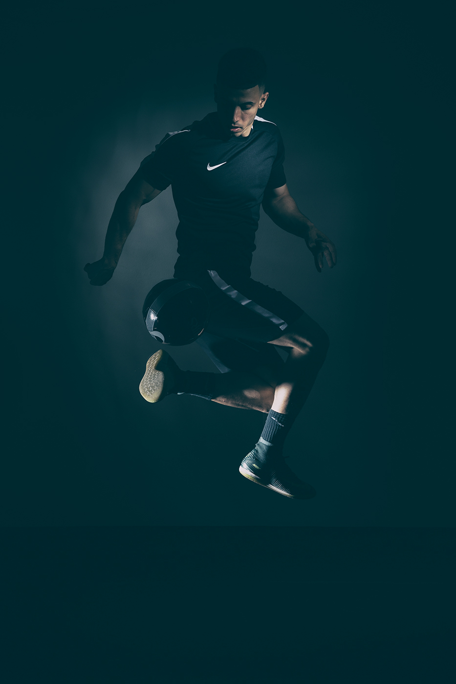 Soccer player doing a ball trick indoors with dramatic lighting