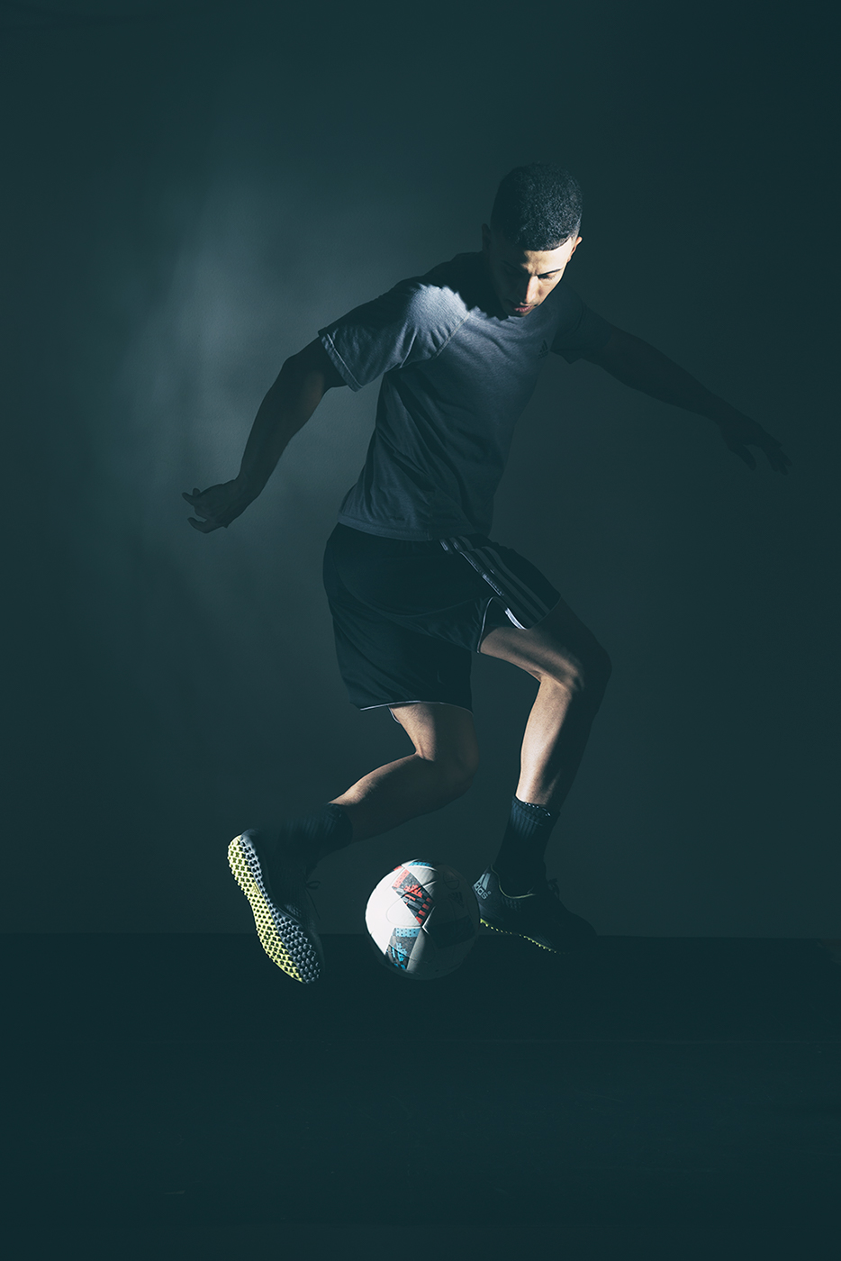 Commercial photographer Portland - man dribbling ball in dramatic light