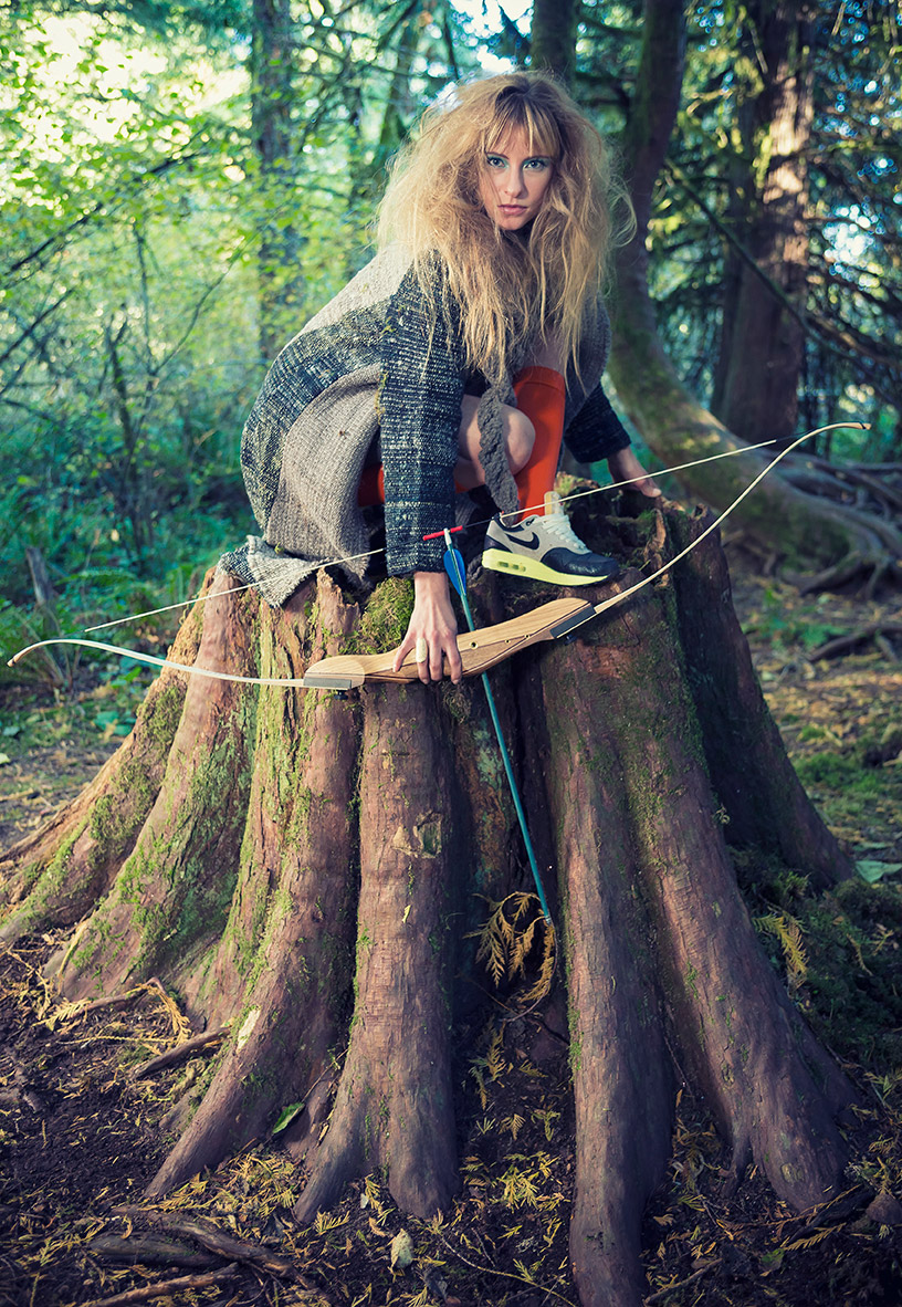 Fashion photography Portland - woman with bow and arrow on a tree stomp