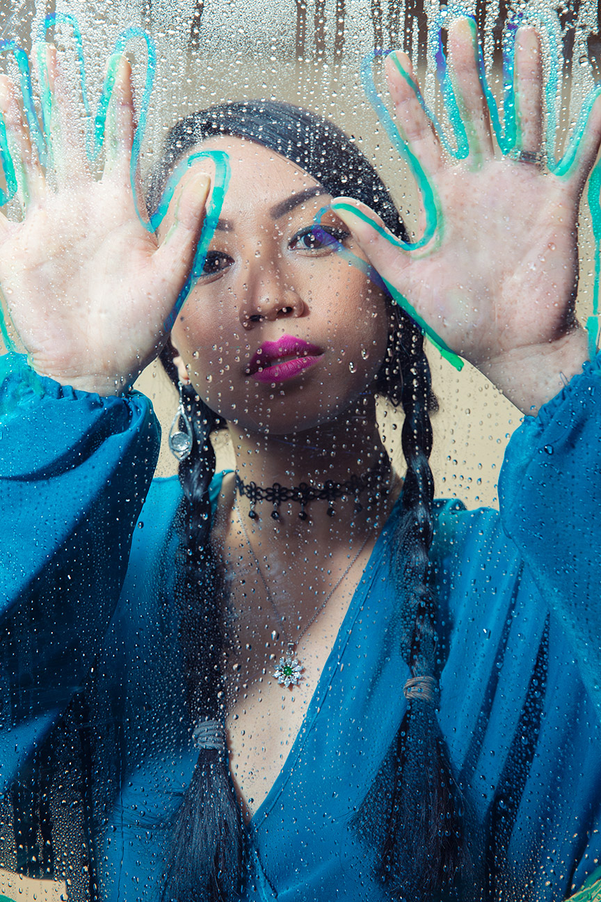 Portrait photography Portland -Asian American woman in a blue blouse with her hands on plexiglass