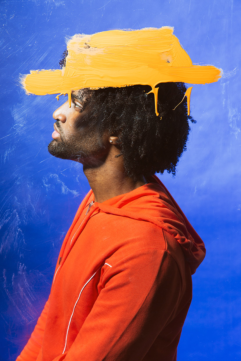 Editorial photographer Portland - Man in orange hoodie with painted orange hat