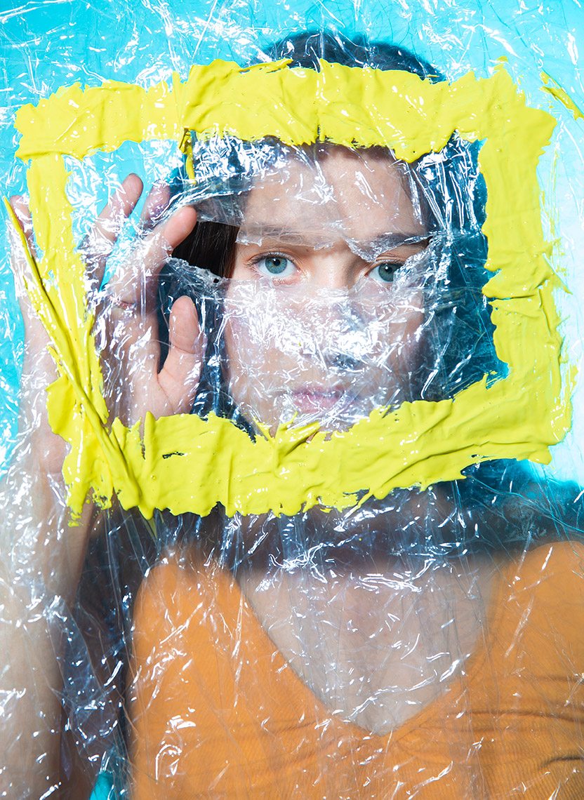Commercial photography Portland - woman looking through ripped plastic with yellow painted square
