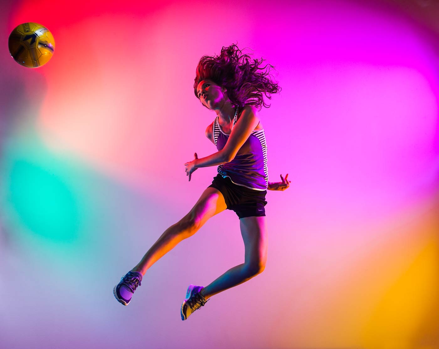 Commercial photography Portland - woman surrounded by color kicking a soccer ball