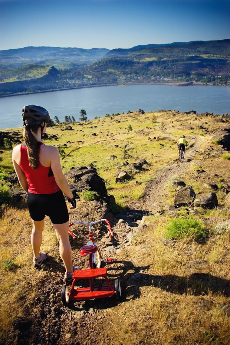 Woman with a tricycle on a steep hill looking down a path with the Columbia River Gorge below.