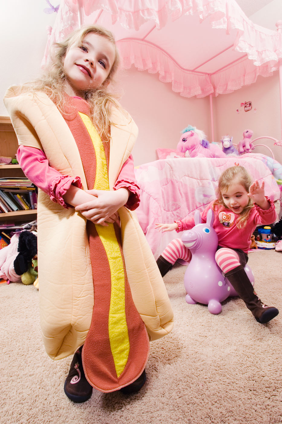 Portland editorial photography -girl dressed up as an Oscar Mayer hotdog in a pink room with her sister